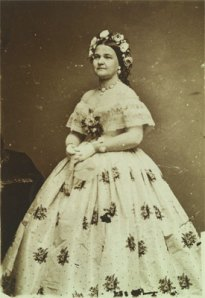 Mary Todd Lincoln in a photograph by Mathew Brady, November 1861, in a heavy white silk dress onto which Washington modiste Elizabeth Keckley had sewn 60 velvet bows and countless black dots.