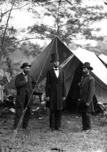 "Allan Pinkerton, President Lincoln, and Major John A. McClernand in an 1862 photo by Alexander Gardner following the Battle of Antietam. Pinkerton was the head of Union Intelligence Services then. It was alleged that, in 1861, his Pinkerton Detective Agency uncovered an assassination plot against the president in Baltimore on his way to the inauguration. Thanks to Pinkerton's warning, Lincoln changed his travel itinerary and the plot was foiled. On the 3-story Chicago building of the Pinkerton Detective Agency, their logo, a black-and-white eye, says ""We Never Sleep."" This was the origin of the slang term for detective ""private eye."""