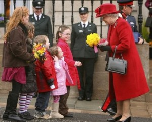 Britain's Queen Elizabeth II (R) receives flowers from children as she departs St Patrick's Cathedral in Armagh, Northern Ireland, March 20, 2008. The Queen handed out Maundy Thursday alms purses to 82 men and 82 women, the presentations are in recognition of their services to both church and community.
