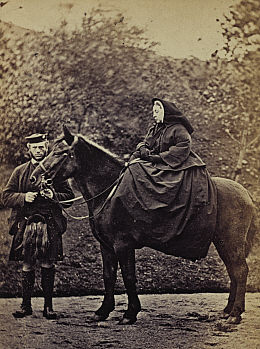"The recently widowed Queen Victoria wearing mourning clothes at Balmoral, Scotland, 1863. She is riding ""Fyvie"" and is accompanied by her faithful servant John Brown. Her husband, Prince Albert died in December of 1861 of typhoid fever or perhaps cancer of the stomach. For forty more years, the rest of Victoria's life, she wore black widow's weeds. Suspicion was aroused by Victoria's partiality to John Brown as a servant; most of the members of the Royal Household referred to him as ""the Queen's stallion"" and defamatory pamphlets referred to her a ""Mrs. Brown."" A 1997 film with Judy Dench titled ""Mrs. Brown"" was about the possible love affair."