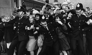 Beatlemania. October 1965, London, England, UK.  Policemen struggle to restrain young Beatles fans outside Buckingham Palace as The Beatles receive their MBEs (Member of the British Empire) in 1965.