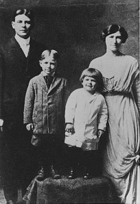 "A photograph of Ronald Reagan as a young child. He is standing between his mother and older brother, Neil. Notice his Dutchboy haircut, from which he got the nickname, ""Dutch."""