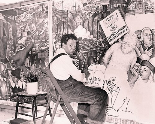 Diego Rivera, seated in front of a mural depicting the American class struggle, 1933.