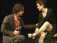 """Sean Lennon, the son of John Lennon and Yoko Ono, cuts away a piece of his artist mother Yoko Ono's dress as she repeats her 1960s performance """"Cut Piece,"""" in Paris.  (AP)"""