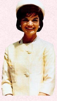 First Lady Jackie Kennedy displays her trademark chic - pillbox hat, pearls, and stylish suit