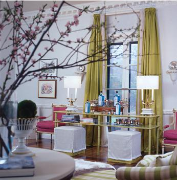 A modern room with touches of Schiaparelli pink in the two chairs and flowers in foreground