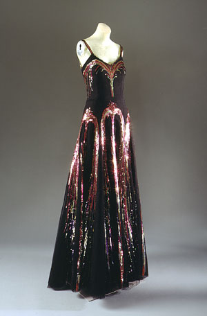 """Evening Dress,"" 1938. Gabrielle (""Coco"") Chanel. Black Silk Net with Polychrome Sequins. The Metropolitan Museum of ARt, New York. Special Exhibit: ""Blithe Spirit: The Windsor Set"" The decoration of sequined fireworks on this evening dress, which was worn by the Countess Madeleine de Montgomery to Lady Mendl's seventy-fifth birthday party in 1939, is a fitting climax to le beau monde of the 1930s. It was the end of an era when, on Sept. 1, 1939, Parisians heard an early-morning radio announcemen from Herr Hitler in German, at once translated into French, that ""as of this moment, we are at war with Poland."" The thirties were over; the Second World War had begun."