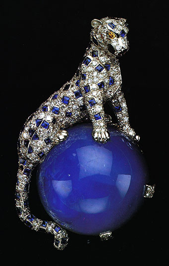 In 1949, the Duchess of Windsor acquired this diamond and sapphire panther pin from Cartier. The panther is crouched in a life like pose on a large perfect round cabochon star sapphire weighing 152.35 carats. This panther pin was one of the Duchess' favorite pieces which she frequently wore. It created an envy among other jewelry collectors and a demand for Cartier to produce more panther pieces. Today, the panther is a Cartier icon. The Duchess of Windsor's animal pieces became her signature.