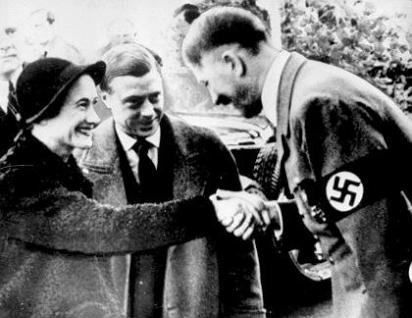 Adolf Hitler kisses the hand of the Duchess of Windsor as her husband the Duke looks on, admiringly. The Duke and Duchess of Windsor visited Germany in 1937 before WWII broke out across Europe. They were outspoken supporters of Nazi fascism and suspected of spying for Germany. At the beginning of the war, the Windsors were whisked out of France to safe haven in the Bahamas, where the Duke served out the war years as governor. There he could do Britain little harm - and he was less likely of being kidnapped by the Germans who were reportedly interested in installing him as a puppet king in a conquered Great Britain under German rule.