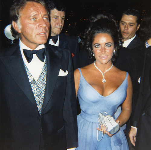 Richard Burton escorts wife Elizabeth Taylor in an Edith Head evening gown, 1970