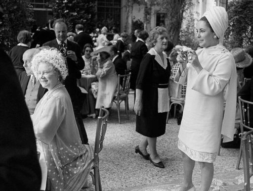 At a 1968 British society wedding in Kent, Hollywood legend Elizabeth Taylor snaps a souvenir picture of the Queen Mum (seated), mother of Queen Elizabeth II. The Queen Mum