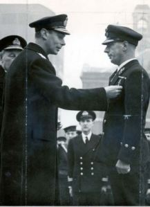 King George VI pins a Distinguished Service Medal on Chief Petty Officer C.L.Baldwin in December 1939.