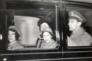 King George VI and his family leave Buckingham Palace, 1939, to spend Christmas at their country house at Sandringham. Pictured are the King and his wife Queen Elizabeth, daughters Princesses Elizabeth and Margaret Rose. Princess Elizabeth would become Queen Elizabeth upon the death of her father in 1952.