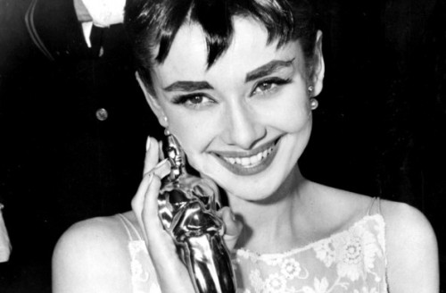 "1953 Audrey Hepburn grins upon receiving her Oscar for ""Roman Holiday."""