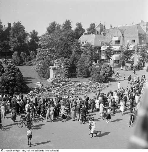 The Queen Emma monument is festooned with flowers on Carnation Day, 1940