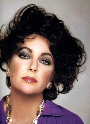 Elizabeth Taylor, age 44, wears her signature color, purple, to match her violet eyes. 1977