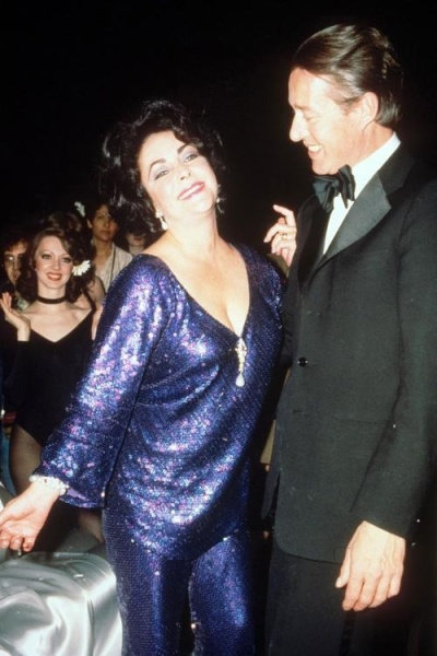 Elizabeth Taylor dances with her fashion designer friend Halston at Studio 54. Note that Elizabeth wears a purple pantsuit. Feb. 1978