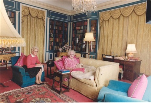 British romance novelist Barbara Cartland dictates stories to her secretary while relaxing with one of her Pekinese pets.