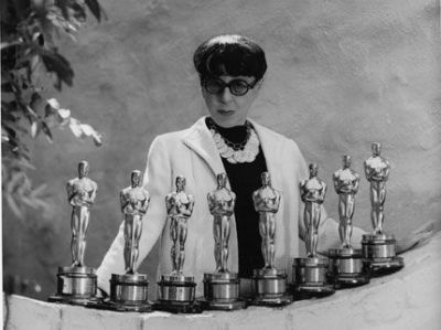 Legendary costume designer Edith Head (1897-1981) displays her 8 Oscar trophies. Originally, she wore blue tinted glasses because it allowed her to view fabrics as they would look in a black-and-white movie. Smoky lenses also made her inscrutable as well as disguising a slightly-crossed right eye. Undated photo