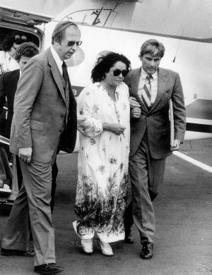 Elizabeth Taylor is assisted by her husband, John Warner (r.) as she returns from a hospital stay in Richmond, Va. Oct. 13, 1978
