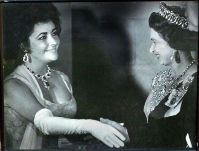 At a British Embassy reception, Queen Elizabeth II of England gets a look at Elizabeth Taylor's famous jewels: the Bulgari Vladimir Suite of emeralds and diamonds from her soon-to-be-ex-husband, Richard Burton. July 1976