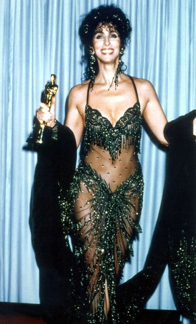 "Cher accepts the Best Actress Oscar for her film role in ""Moonstruck"" at the 1988 Academy Awards. Her costume was designed by Bob Mackie. It made headlines."