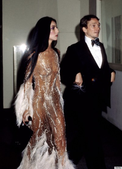 "Cher and her designer Bob Mackie arrive at a Met gala, 1974. She is wearing a Mackie bodysuit embroidered with feathers and crystals. Mackie said of his muse, ""She had such an unbelievable body. She could wear anything."" This outfit would be featured on the cover of ""Time"" magazine the following spring. (1)"