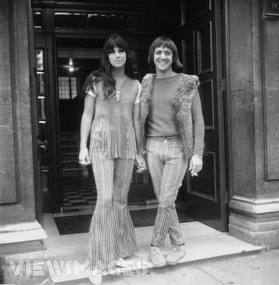 Cher and Sonny wear matching striped bell-bottoms. Sonny often wore a furry open vest, as he is here. ca. 1965