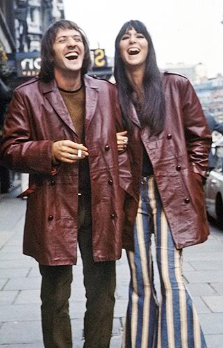 "Salvatore Phillip ""Sonny"" Bono (1935-1998) and Cherilyn Sarkisian (b. 1946) AKA known as the American singing duo, Sonny & Cher, are shown here in their trend-setting unisex fashion. 1965."
