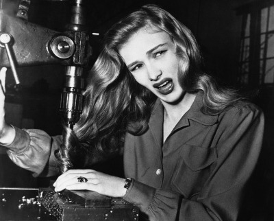 In this Life magazine photo, movie star Veronica Lake illustrates the danger of loose hair for female factory workers. Her hair is tangled in machinery. Photo Undated. Ca. 1943