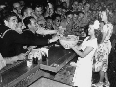 Film star Shirley Temple gives cookies to the soldiers at the Hollywood Canteen. Ca. 1942-45.