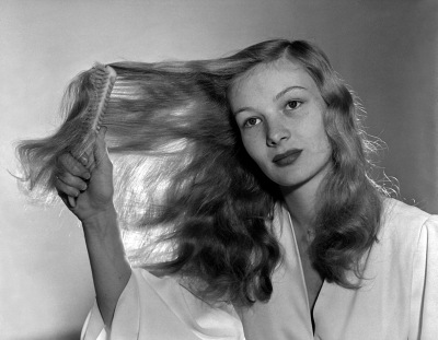 Constance Keane brushes her lustrous honey-blond hair. Undated photo. ca. 1940