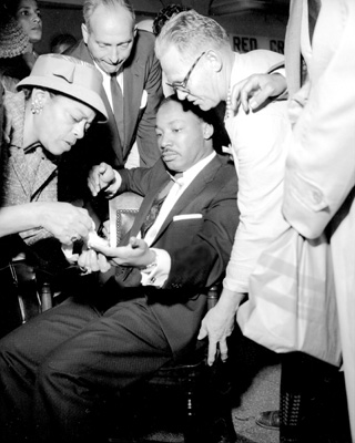 Dr. Martin Luther King, Jr. sits calmly with a letter opener protruding from his chest as Nettie C. Jackson tends his cut hand. September 20, 1958